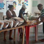 Homem e mulheres distribuindo alimentos sobre mesas no Estado do Ceará